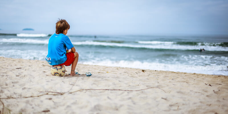 Child Sitting on a ball on the beach