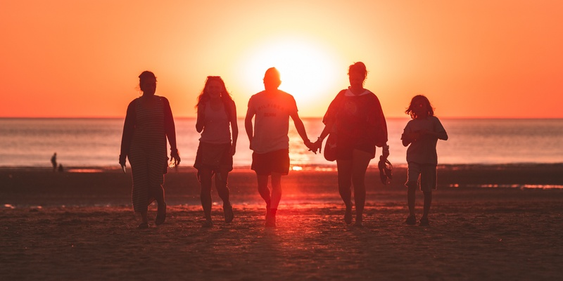 Family holding hands at sunset symbolising wills.
