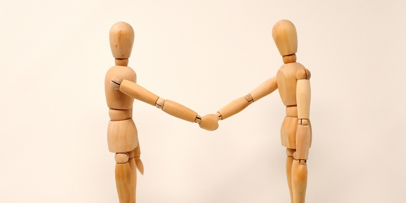 Wooden figures shaking hands in agreement symbolising terms and conditions