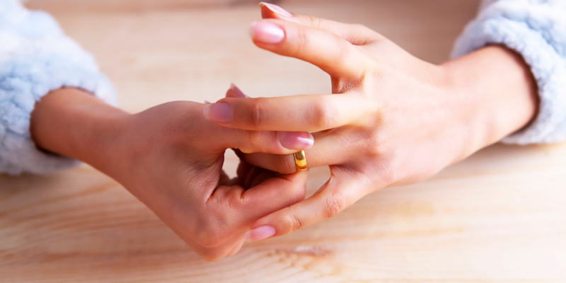 Woman taking wedding ring off symbolising divorce