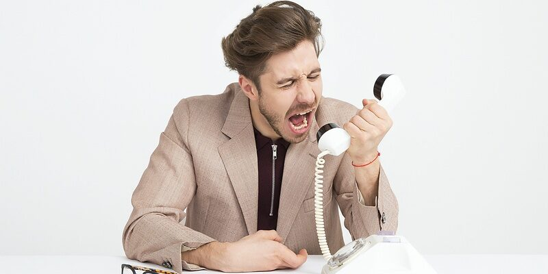 Workplace bullying: a man shouting into a desk telephone