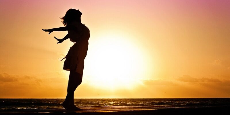 Woman stretching at sunset signifying divorce and a new start