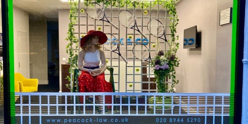 Peacock & Co Wimbledon Championships window display of mannequin in red hat and skirt, white top and tennis racquets on a trellis.